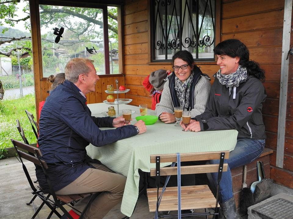 Auf der Veranda sitzt Kurt Aeschbacher Silvia und Simone Ueberschlag am Tisch gegenüber. Die beiden Frauen tragen Schals. Kaffee im Glas wärmt auf.