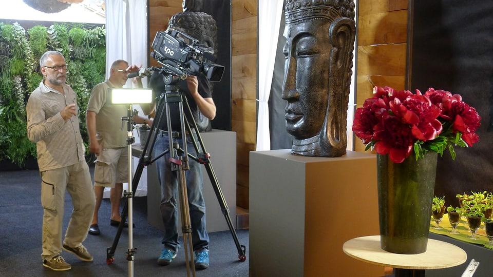 Der Strauss Pfingstrosen wird für Nahaufnahmen bereitgestellt. Beleuchter Andreas Hagen und Tonoperateur Ruedi Guyer stehen leicht nach hinten versetzt zum Kameramann Jörg Glaser, der die Blumen im Visier hat.