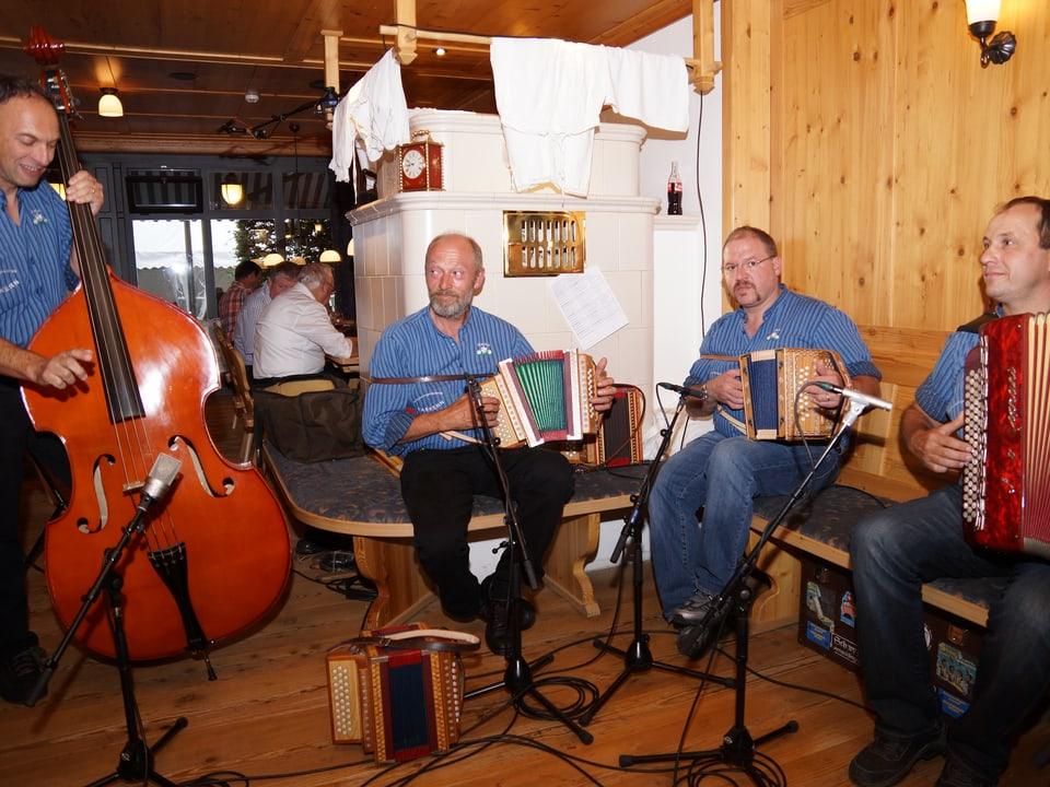Vier Musikanten mit Bassgeige, Schwyzerörgeli und Akkordeon beim Musizieren.