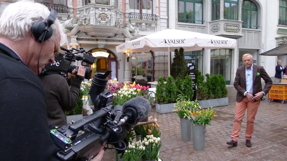 In der Schaffhauser Altstadt steht Kurt Aeschbacher parat für eine Moderation. Die beiden Kameramänner halten ihre Filmkamera bereit.
