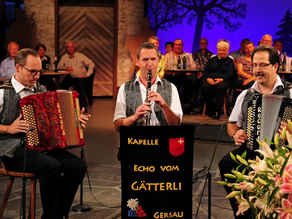 zwei Akkordeonspieler nehmen den Klarinettisten in die Mitte.