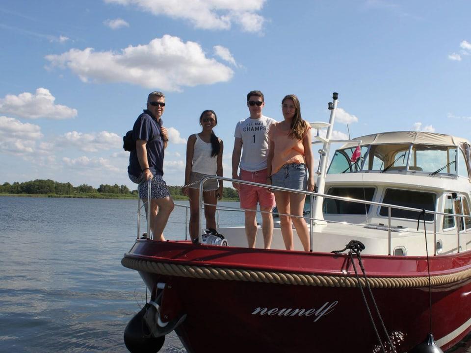 Mann posiert mit seinen drei Kindern auf einer Yacht.