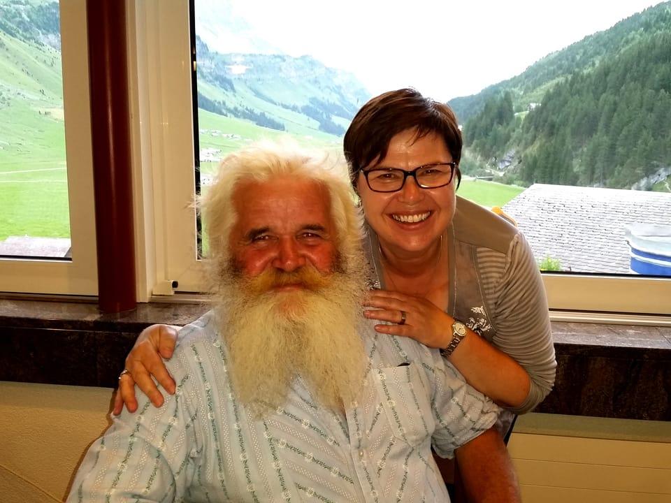 Toni Arnold sitzt, Christine Gertschen steht mit den Händen auf Arnolds Schultern.