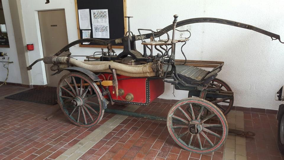 Ina pumpa veglia (in car cun rodas da len cun tschertgels da metal) da Ramosch en il local da pumpiers a Danuder.