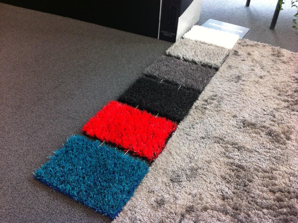 Weiss, rot, blau, schwarz, grauer Kunstrasen.