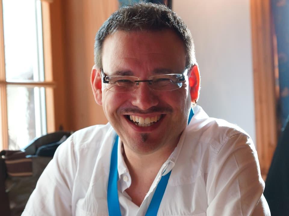 Schnappschuss von Guido Rüegge, der ein weisses Hemd trägt.