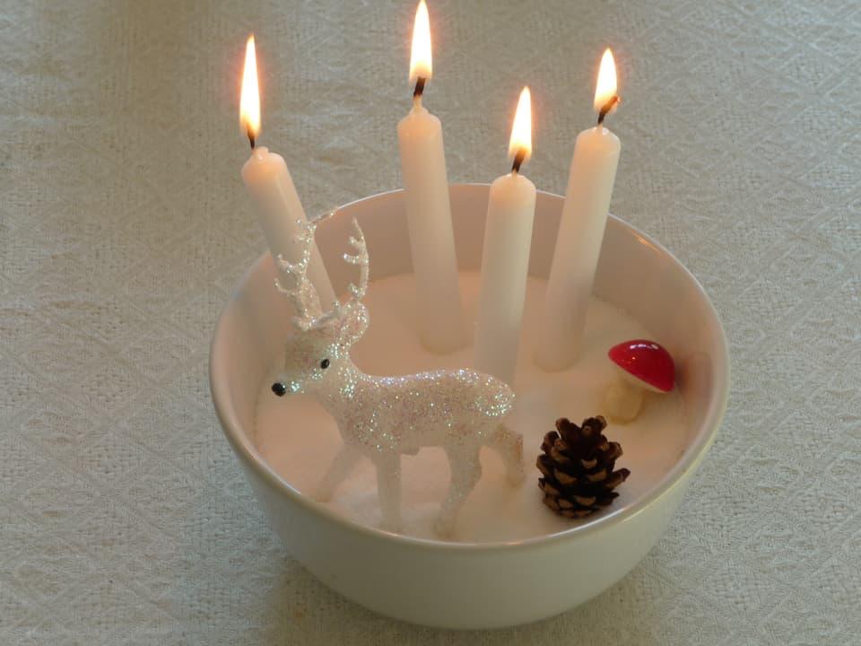 Gefäss mit Streusalz. Darin stecken vier Kerzen.
