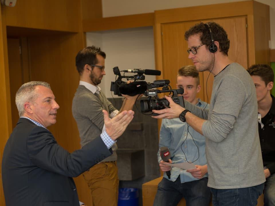 Zwei Kameramänner filmen Reto Lipp und Schüler.
