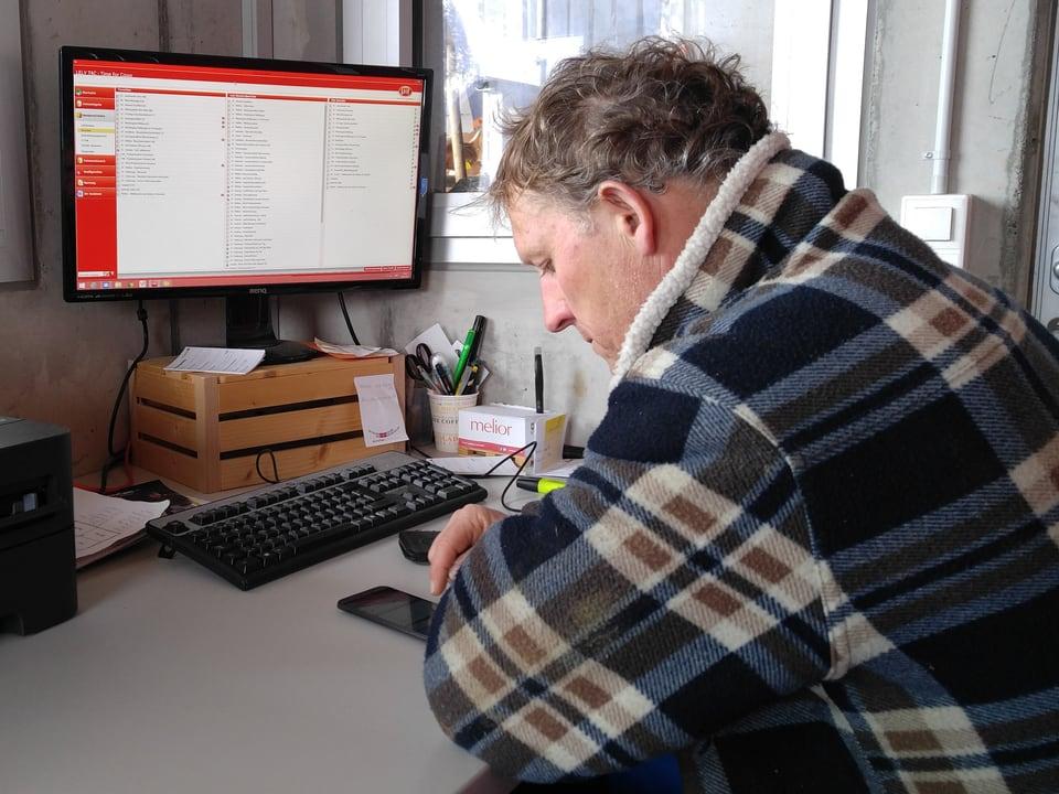 Jürg Oberli tippt an seinem Smartphone herum, sitzend im Büro vor dem Computer.