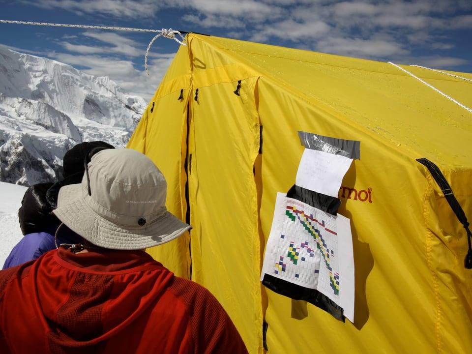 Zwei Teilnehmer stehen vor einem Zelt, an dem Pläne aufgehängt sind.