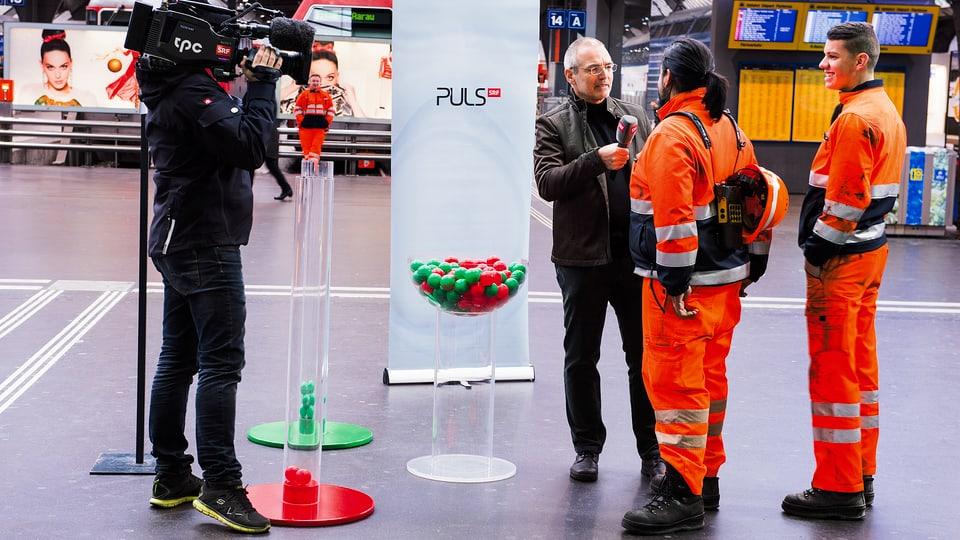 Pulsarzt interviewt zwei Männer.