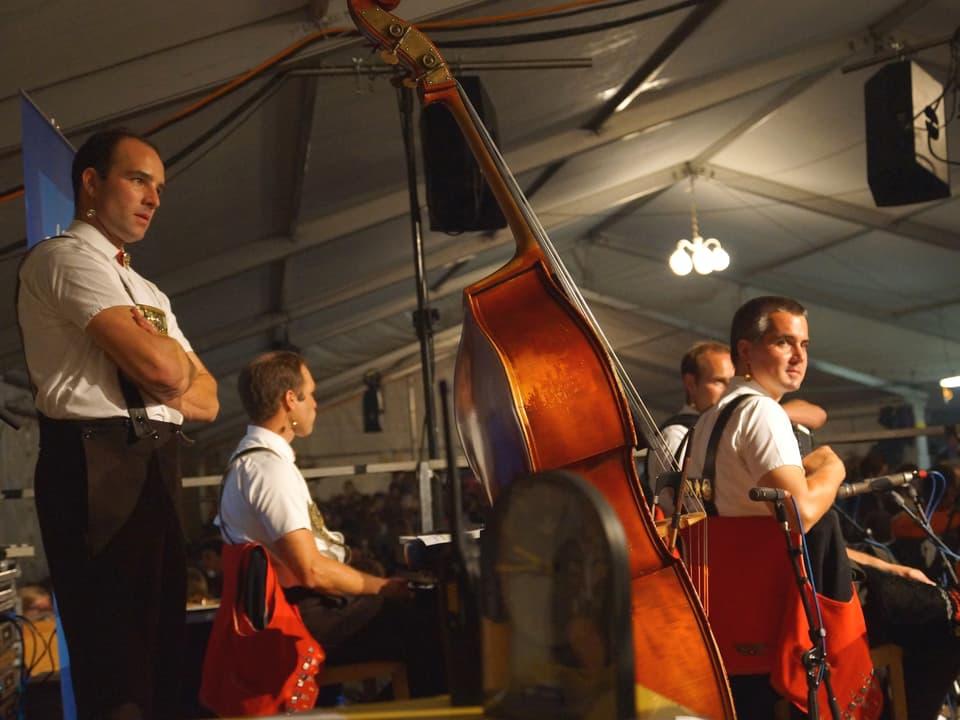 Die Musiker haben ihre Instrumente beiseite gelegt und ruhen sich sitzend oder stehend etwas aus.