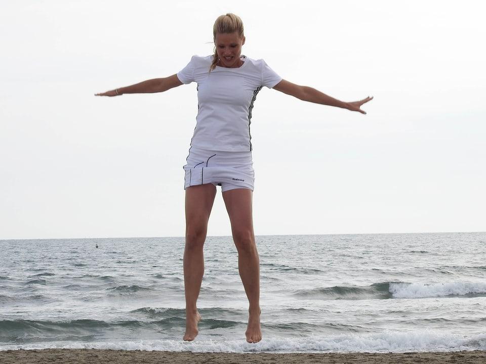 Michelle Hunziker springt am Strand in die Luft. Im Hintergrund ist das Meer zu sehen.