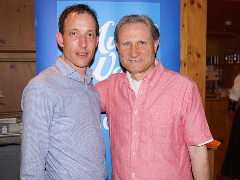Farbig komponierter Schnappschuss: Der Gast trägt ein hellblaues Hemd, der Moderator ein rosafarbenes.