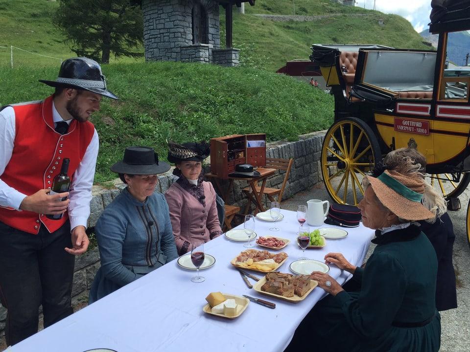 Vier Damen sitzen an einem Tisch mit Käse, Fleisch, Trauben und Weingläsern.