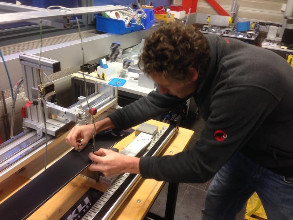 Mann beugt sich mit einem Messgerät über einen Ski .