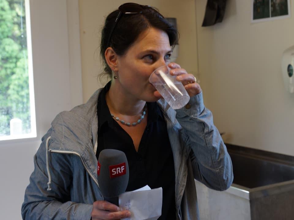 Die SRF Musikwelle-Moderatorin hält in der einen Hand ein Mikrofon, in der anderen ein Glas Mineralwasser.