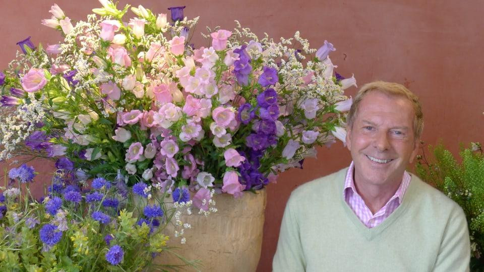 Nahaufnahme von Kurt Aeschbacher neben einem riesigen Tontopf, gefüllt mit weissen, violetten und lilafarbenen Glockenblumen.