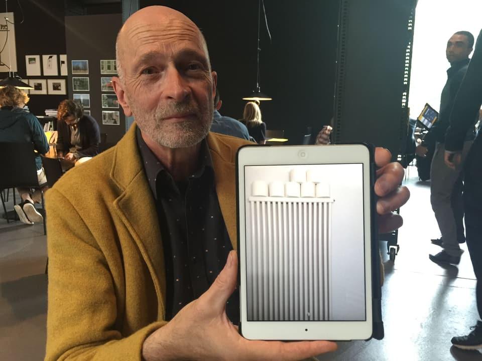 Roland Tinguely hält ein iPad in die Kamera mit einem Kunstwerk darauf.