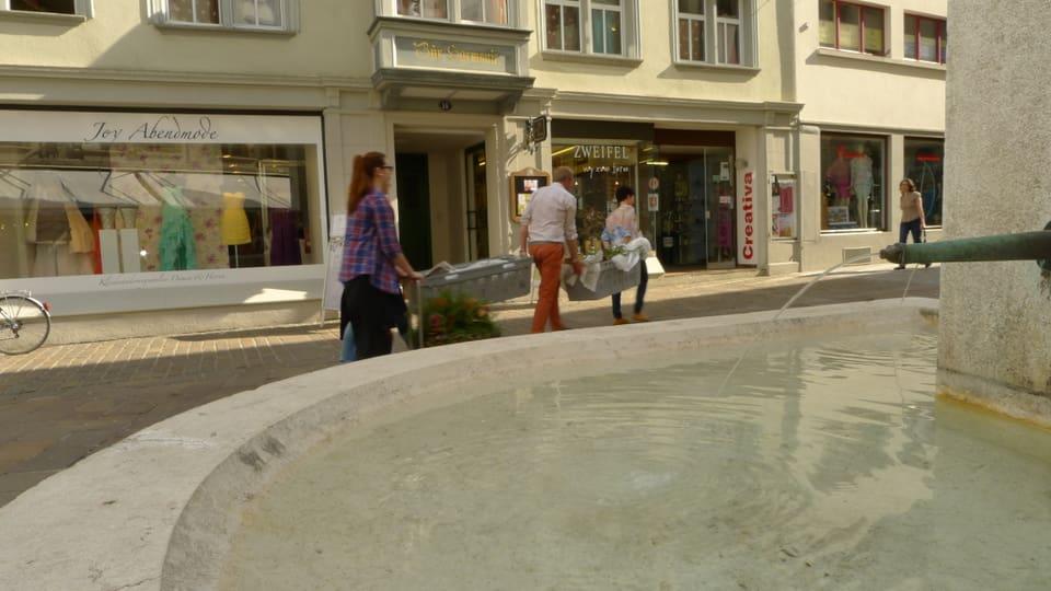 Der Floristen-Transport trägt die beiden grossen Blumenkisten durch die Sankt Galler Altstadt, vorbei an einem Brunnen. Im Hintergrund sind Geschäfte zu erkennen.