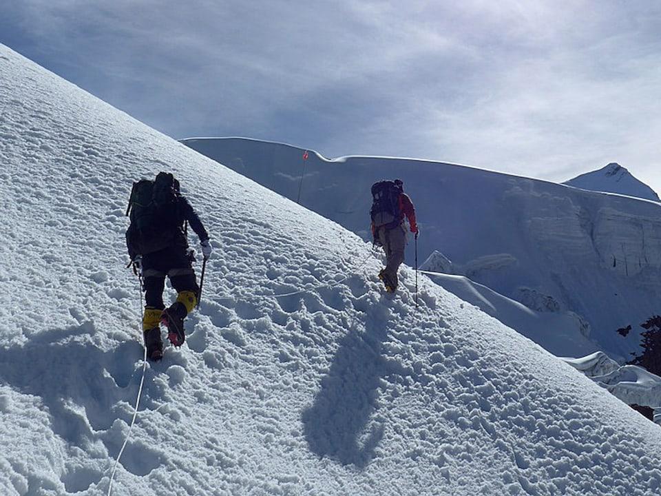 Alpinisten gehen am Seil.
