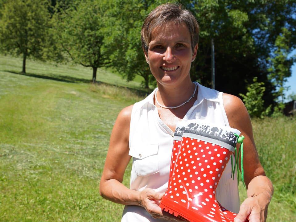Jolanda Brändle trägt eine weisse kurzärmlige Bluse und steht auf einer Wiese, wo sie rote Gummistiefeln mit weissen Punkten zeigt, die obenen ein Scherenschnittmuster haben.