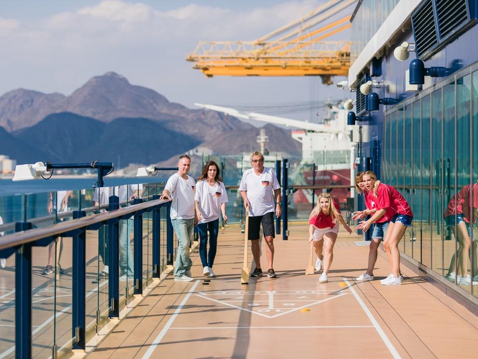Team Schweiz und Team Deutschland spielen Shuffleboard auf dem Schiffsdeck