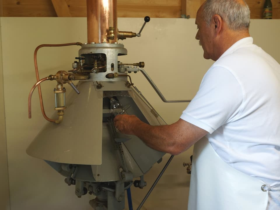 Ruedi Preisig im weissen Polo-Shirt und mit weisser Schürze vor der antiken Maschine aus Kupfer und Messing.