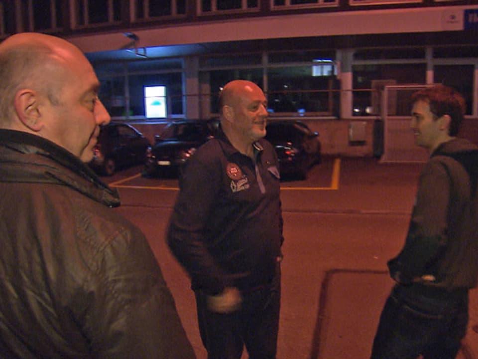 Drei Männer stehen auf der Strasse und diskutieren.