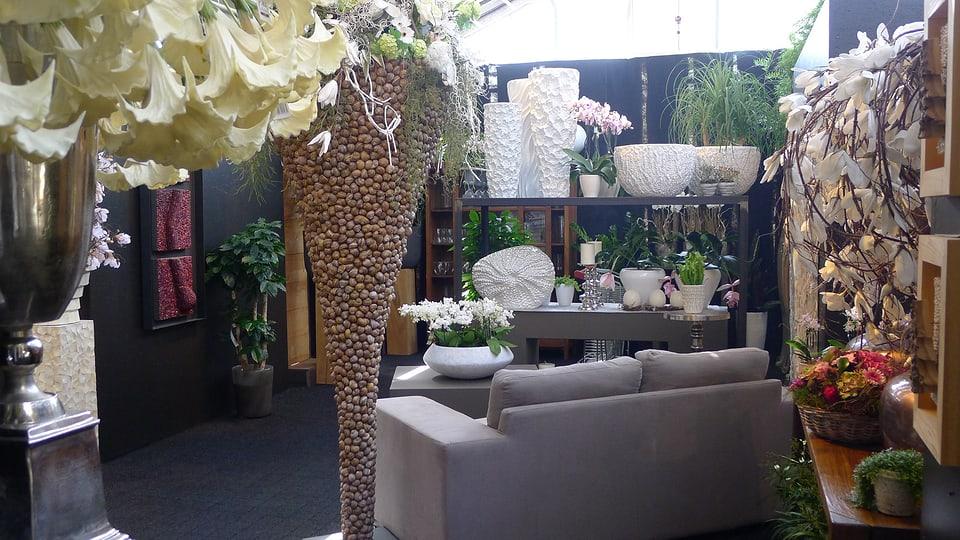 Eine stimmungsvolle Ecke mit verschiedenem Dekormaterial, Schalen, Grünpflanzen und Gestecken. Ein helles Sofa lädt zum Verweilen ein. Federn, Orchideen und hellgelbe Trompetenblüten runden das Ganze ab.