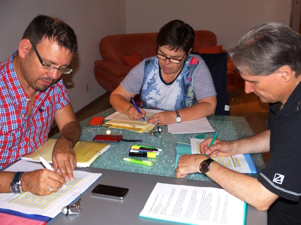 Dir Drei sitzen an einem Tisch über Unterlagen und gehen Seite für Seite durch.