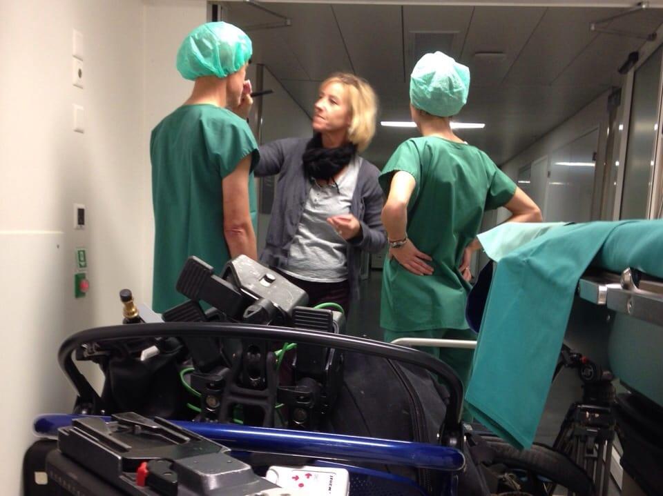 Eine Visagistin pudert einem Arzt das Gesicht.