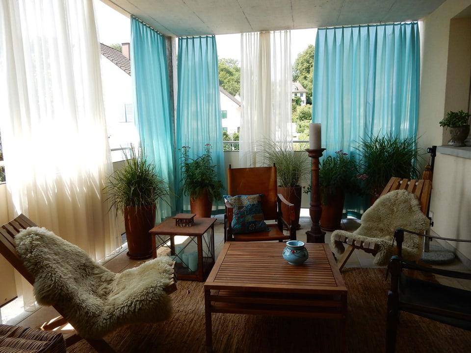 Balkon mit Sitzgruppe und Vorhängen.
