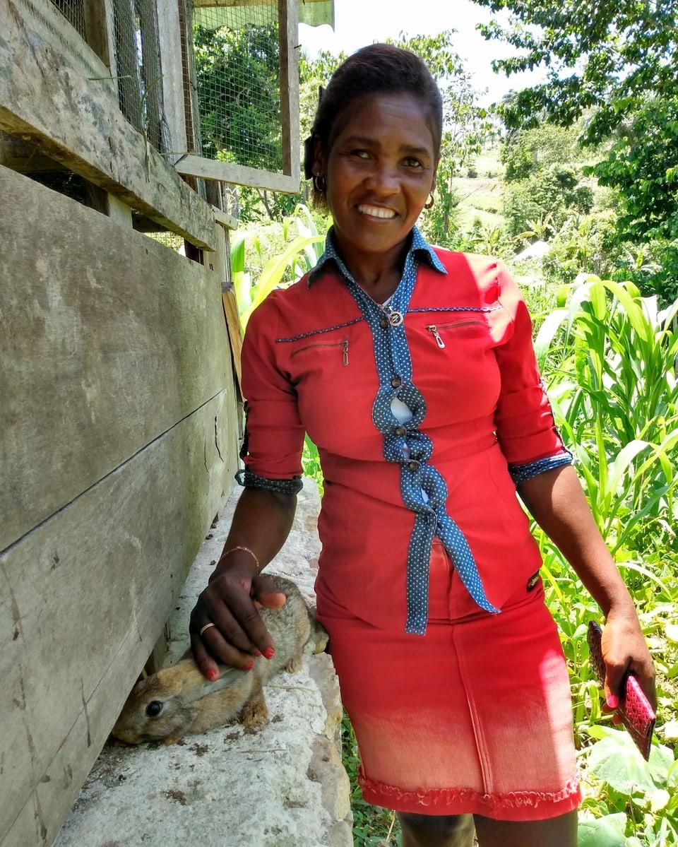 Eine Frau steht vor einem Kaninchenstall und streichelt ein Kaninchen.