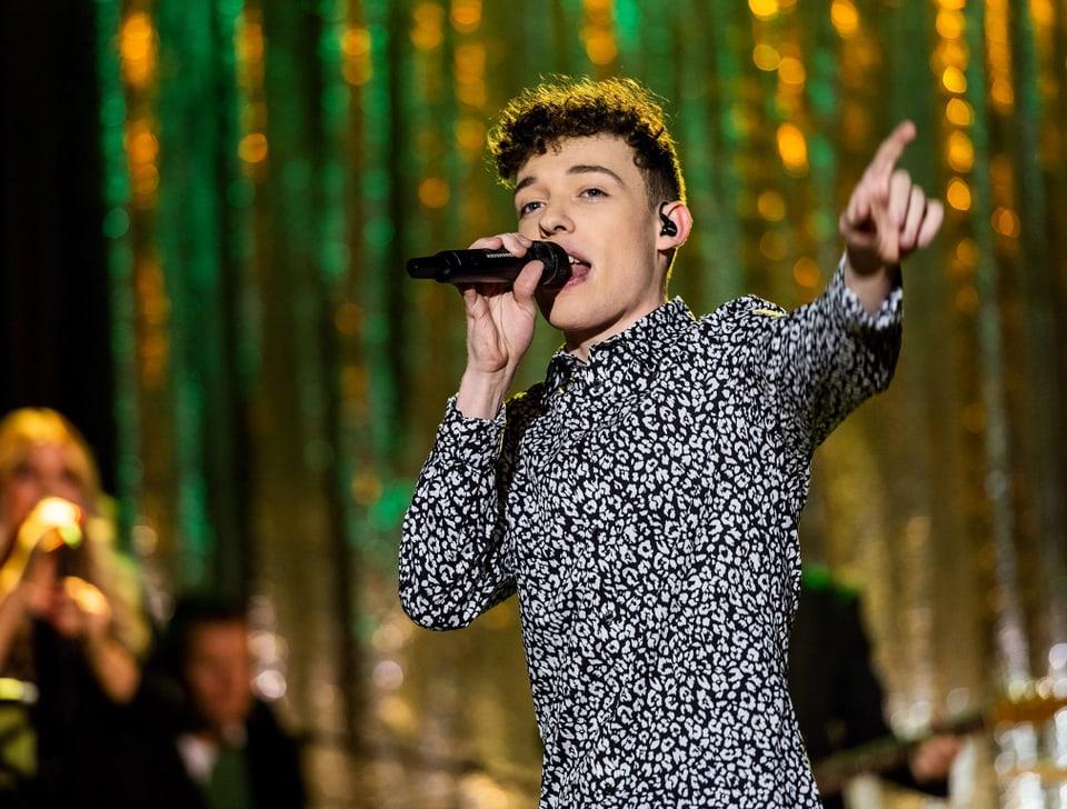 Ein Teenager mit Mikrofon singt ein Lied auf einer Bühne.