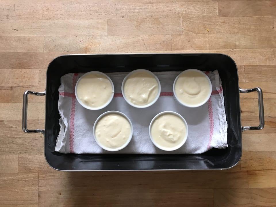 Wasserbad mit Pudding gefüllten Förmchen