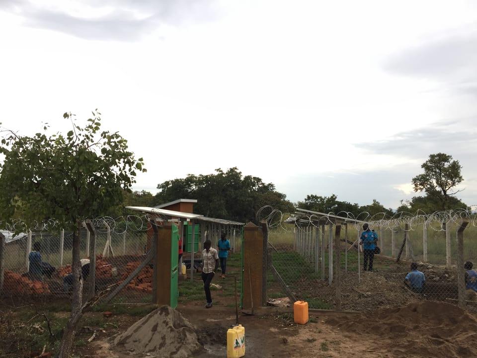 Wasser-Pumpstation im Bau, davor bunte Kanister.