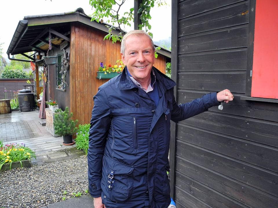 Kurt Aeschbacher in der blauen Regenjacke vor einem dunkel gebeizten Gartenhaus mit rotem Fensterladen.