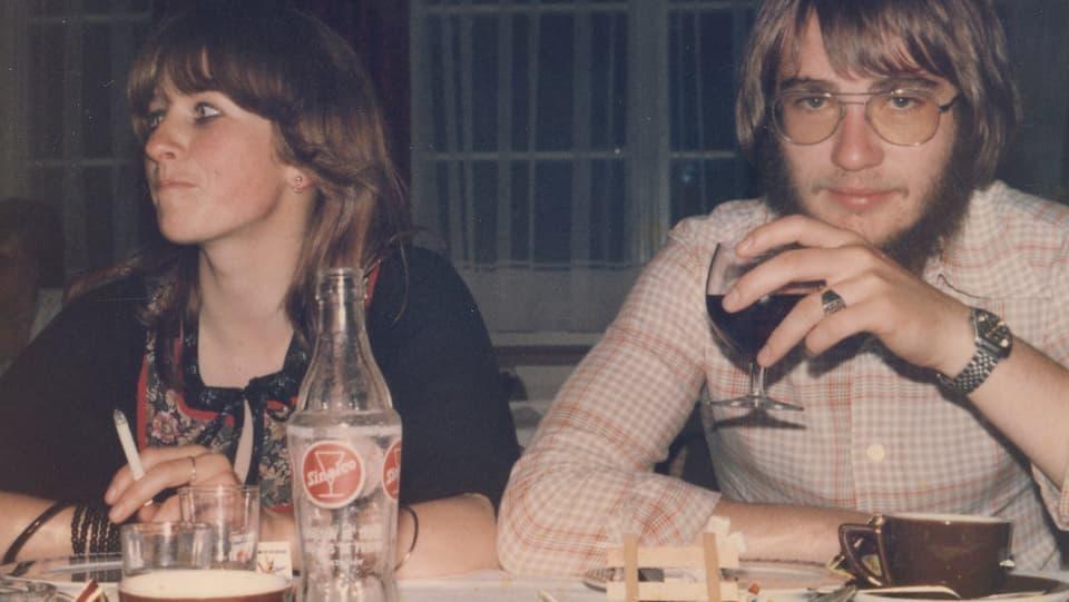 Monica und Erich sitzen am Tisch, trinken Wein und rauchen.