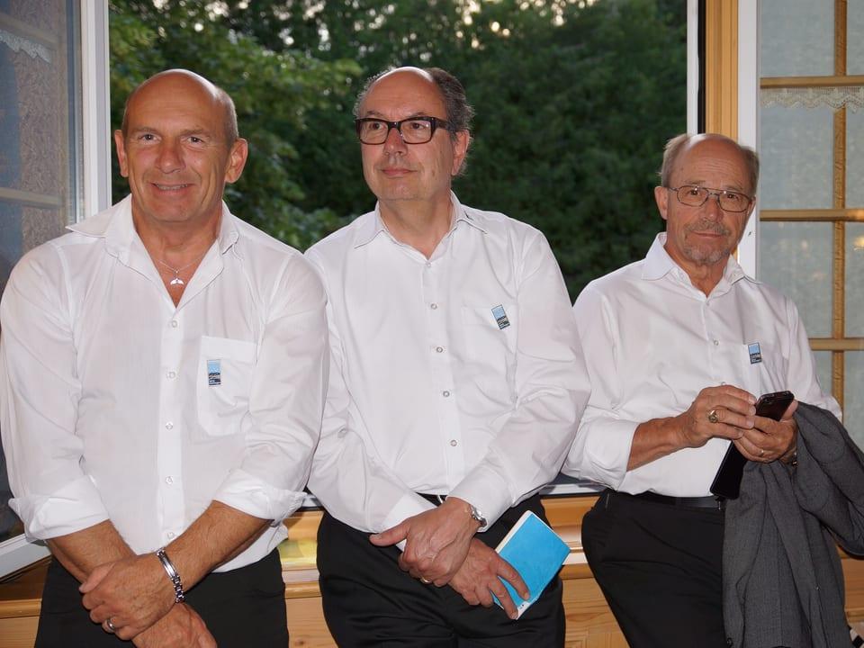 Drei Sänger in weissen Hemden stehen mit dem Rücken vor einem offenen Fenster.