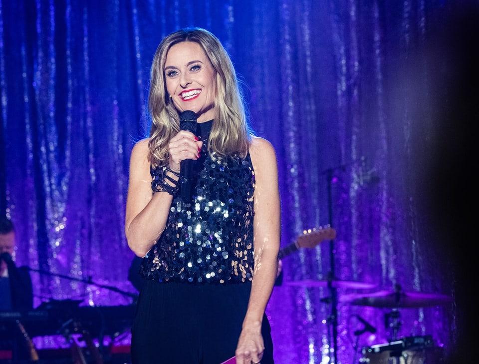 EIne lächelnde Frau mit Mikrofon steht auf einer Bühne