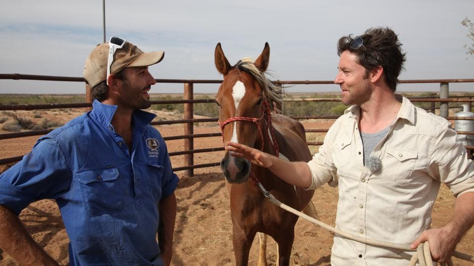 Sven unternhält sich mit Clayton neben einem Wildpferd.