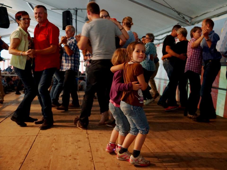 Verschiedene Paare und zwei kleine Mädchen beim Tanzen.