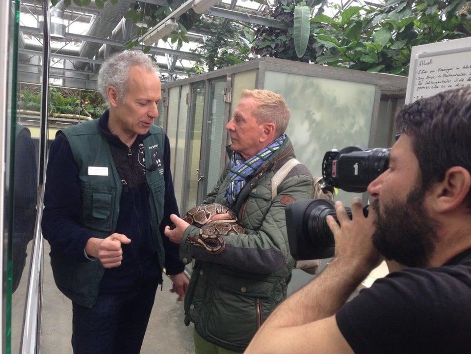 Kurt Aeschbacher hält eine Schlange im Arm und unterhält sich mit Peter Schlup. Ueli Haberstich hält mit seiner Kamera die Szene fest.