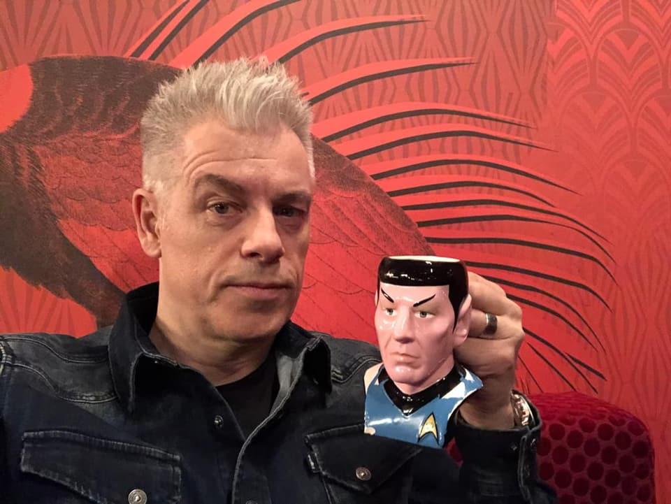 Auf dem Bild ist Komiker Michael Mittermeier, der eine Grimasse zieht und seine Spock-Tasse in die Kamera hält