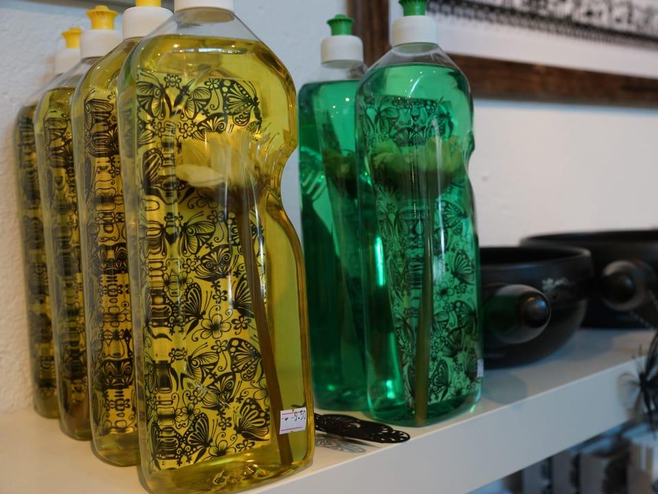 Durchsichtige Flaschen mit gelb und grün gefärbtem Spülmittel und verziert mit Scherenschnitten.