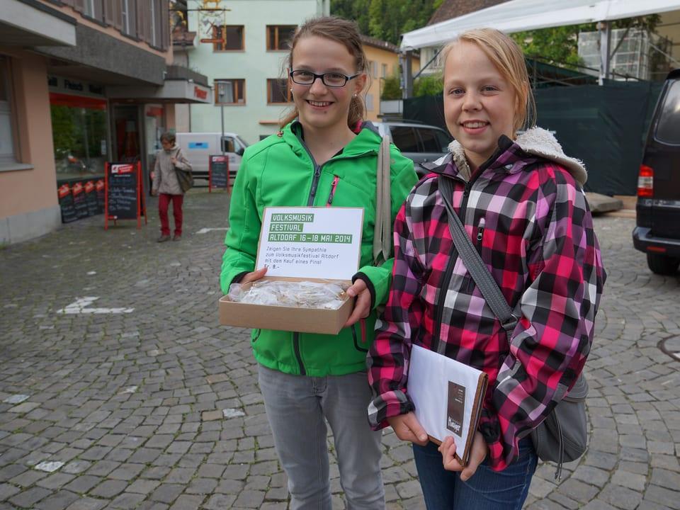 Die beiden Mädchen bieten die Abzeichen den Passantinnen und Passanten an.