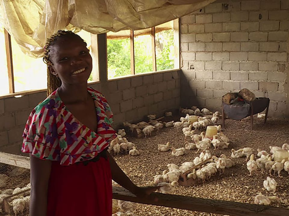Die Bäuerin neben ihrem Hühnergehege.