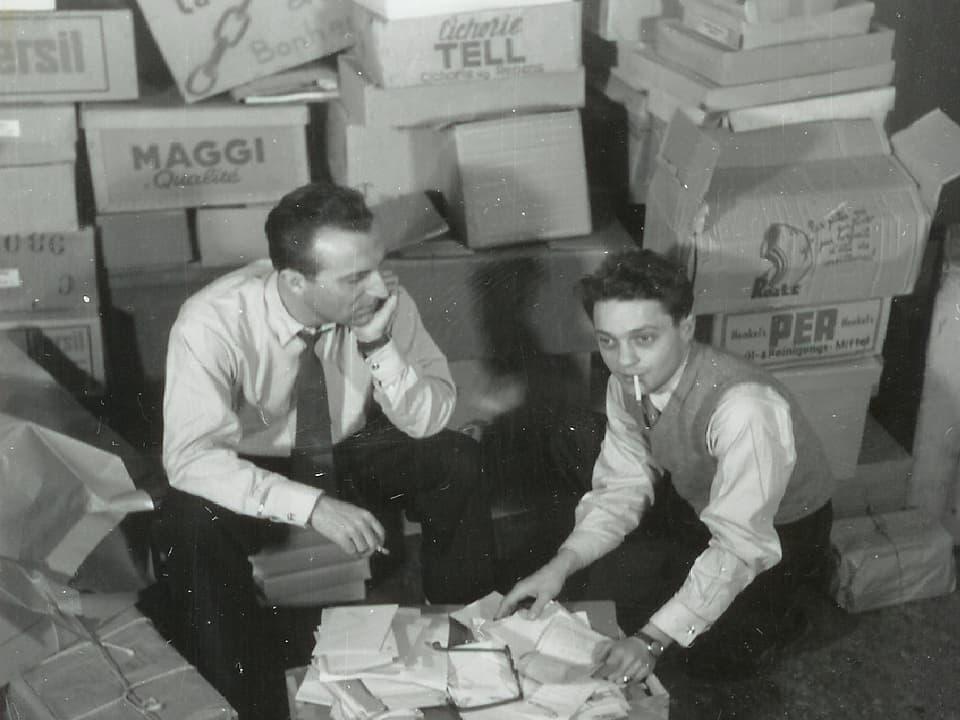 Glückskette-Gründer Roger Nordmann und Jack Rollan knien vor Hilfspaketen.