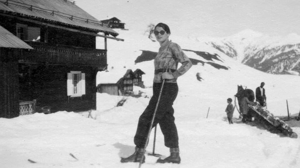 fotografia nair-alva, dunna sin sin skis, davostier in um cun in chaval che tira laina